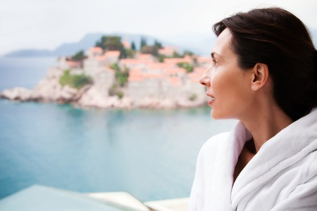 Women on the balcony in background sea and island of Sveti Stefan Montenegro photo
