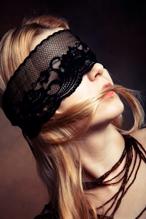 blond woman portrait with black lace over eyes studio shot photo
