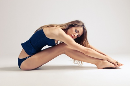 young woman in blue underwear sit on the floor, side view, studio shot, little amount of grain added photo