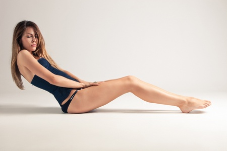young woman in blue underwear sit on the floor, side view, studio shot, little amount of grain added Stock Photo - 9751367