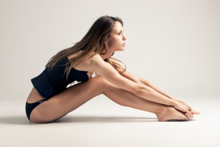 young woman in blue underwear sit on the floor, side view, studio shot, little amount of grain added Stock Photo - 9751369
