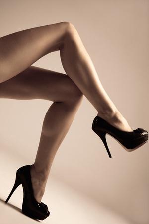 benen: de benen van de vrouw in hoge hak schoenen, studio opname, kleine hoeveelheid graan toegevoegd