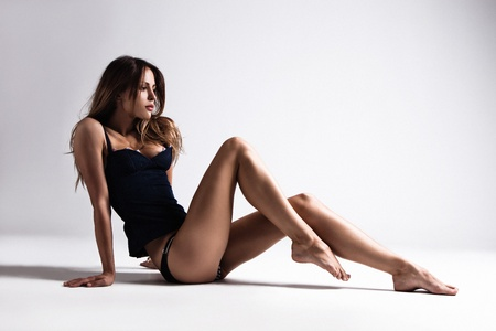 attractive tanned brunette in blue underwear sit on floor, full body shot, small amount of grain added, studio shot photo
