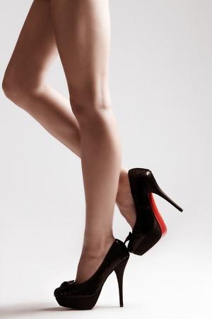piernas sexys: piernas largas delgadas en zapatos de tacones altos, studio dispar� peque�a cantidad de grano agregado Foto de archivo