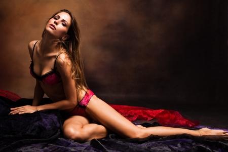 deseo sexual: mujer sensual en ropa interior studio disparo de fondo oscuro