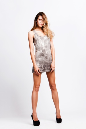 young blond fashion model in short dress on high heels, studio shot Stock Photo - 10019246