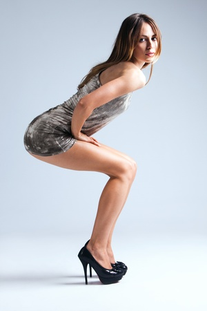 young woman in short dress and high heels, studio shot, full body shot