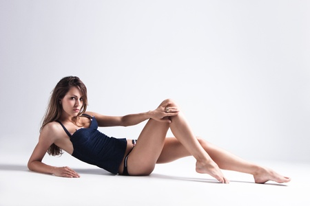 long shot: attractive tanned brunette in blue underwear lie on floor, full body shot, small amount of grain added, studio shot