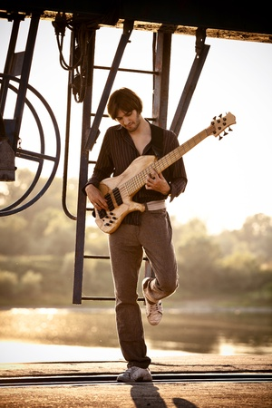 musician: young man play bass guitar at industrial area by the river at sunset, full body shot