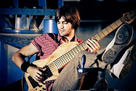 young man play bass guitar at industrial area by the river at sunset Stock Photo - 10019268