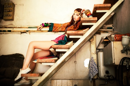young woman in colorfull summer clothes sit on stairs indoor shot photo