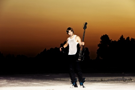young man with his guitar at sunset, full body shot photo