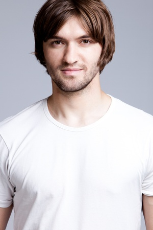young handsome man in white t-shirt, studio shot photo