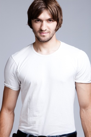 nonchalant: young handsome man in white t-shirt, studio shot Stock Photo