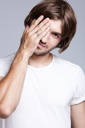 man long hair: young man covers face with hand, studio shot Stock Photo