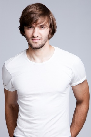 man long hair: young handsome man in white t-shirt, studio shot Stock Photo