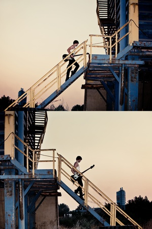going up: young man with electric guitar going up the stairs and down the metal stairs in industrial zone, at sunset