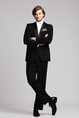 elegant young man in black tuxedo, full body shot,  studio shot photo