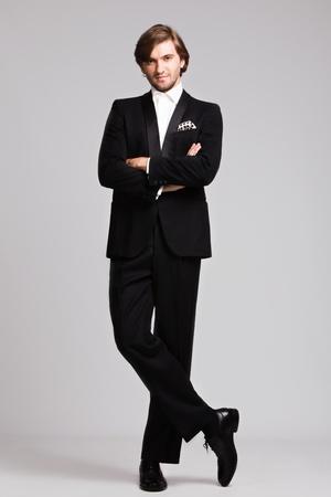 tuxedo man: elegante giovane uomo in smoking nero, colpo di corpo pieno, colpo di studio Archivio Fotografico