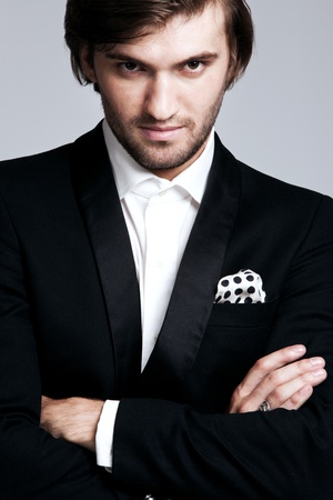 elegant young man in black tuxedo, portrait, studio shot, close up photo