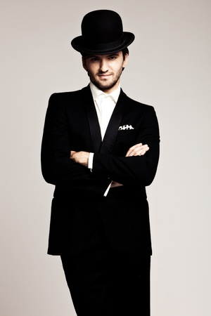 derby: elegant young man in black tuxedo and derby,studio shot Stock Photo