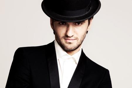elegant young man in black tuxedo and derby,portrait, studio shot photo