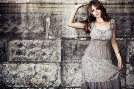 elegance fashion girls look sensuality young: young woman in summer dress  against old stone wall, outdoor shot