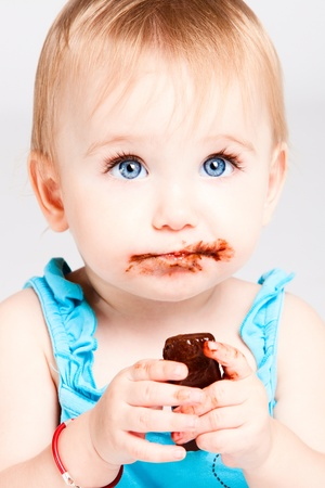 hungry children: beautiful baby girl with blue eyes eat chocolate