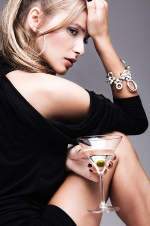 ragazze bionde: moda donna giovane con un bicchiere di martini, profilo, girato in studio
