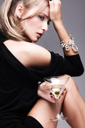 femme chatain: mode femme jeune avec un verre de martini, de profil, tourné en studio