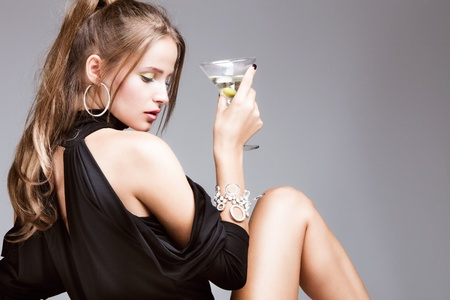 young attractive woman with glass of martini, profile, studio shot photo