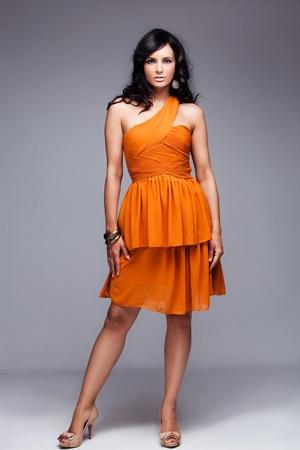cuerpo entero: mujer hermosa cabellera negra en elegante vestido naranja, estudio de disparo, disparo de cuerpo completo