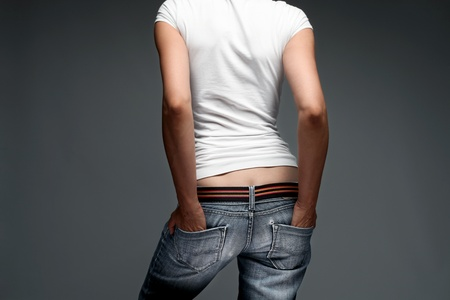 hand in pocket: woman wearing blue jeans and white t shirt, back, studio shot Stock Photo