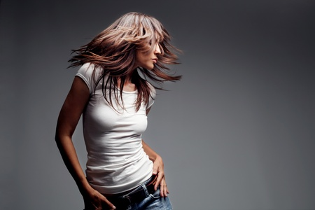 woman flying: woman wearing jeans and white t shirt dancing, studio shot Stock Photo