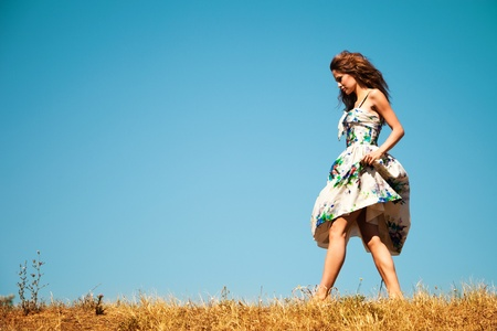 young woman in summer dress walk through the grass, blue sky in background, summer day Stock Photo