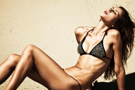 attractive woman in bikini, outdoor shot in sand, summer day photo