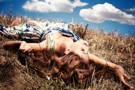 beautiful young woman lie on ground in silk dress, blue sky with clouds in background, summer sunny day photo