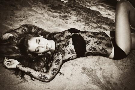 sensual woman lie on beach and smoking photo