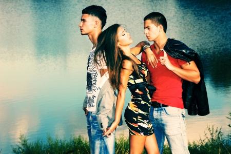 liefde: driehoeksverhouding, twee jonge mannen en jonge vrouw op het strand bij zonsondergang