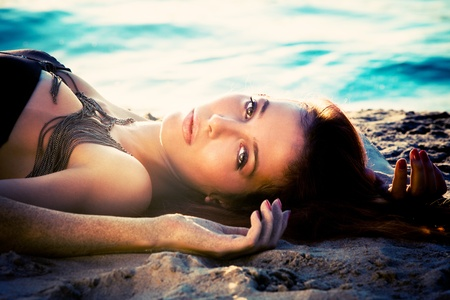 beach model: beautiful woman lie in sand by the river, sunset Stock Photo