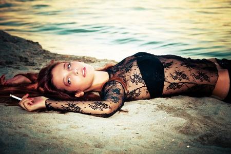 pelirrojas: hermosa mujer de pelo rojo en la puesta de sol en la playa