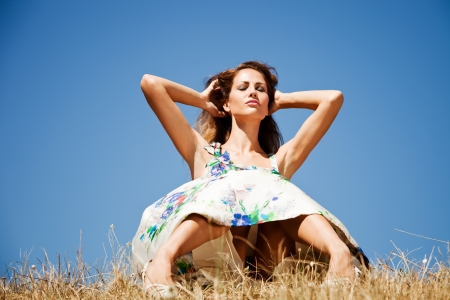 young woman in summer dress sit on grass with  hands in hair  blue sky in background, eyes closed Stock Photo - 10689119