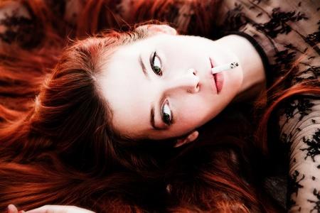 beautiful redhead woman portrait with cigarette photo