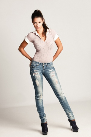 young woman in blue jeans, full body shot, studio, small amount of grain added Stock Photo - 10759653