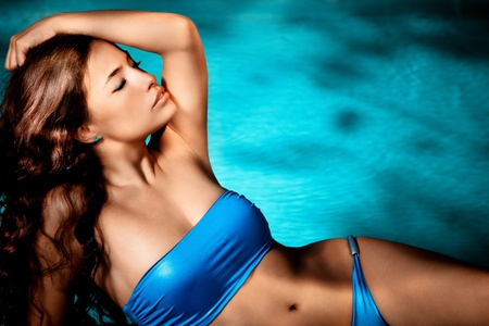 tanned body: beautiful brunette in blue bikini enjoy by the pool