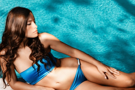 blue bikini: beautiful brunette in blue bikini enjoy by the pool