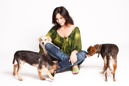 animal woman: happy woman with three adopted street dogs, studio shot Stock Photo