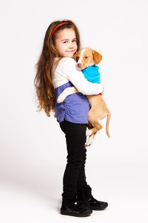 adopted: little girl with her adopted dog, studio shot