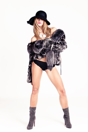 woman in fur, hat and winter boots, studio shot photo