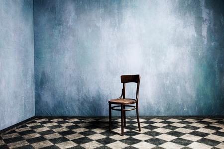 sedia vuota: camera con vecchie pareti blu e pavimento piastrellato con la sedia di legno in mezzo